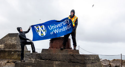 Students holding the UWindsor flag