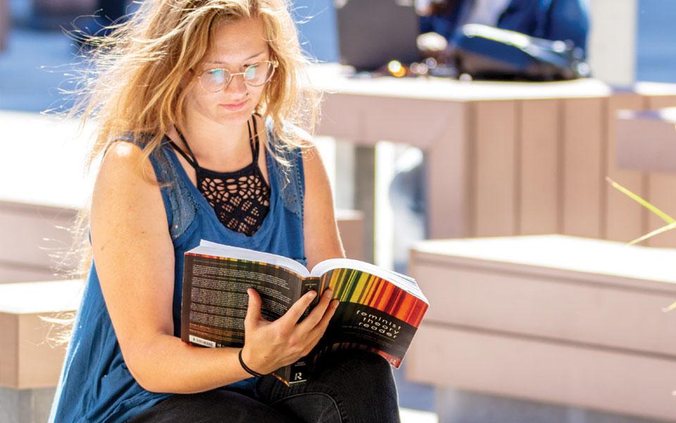 Women's Gender Studies student studying outside