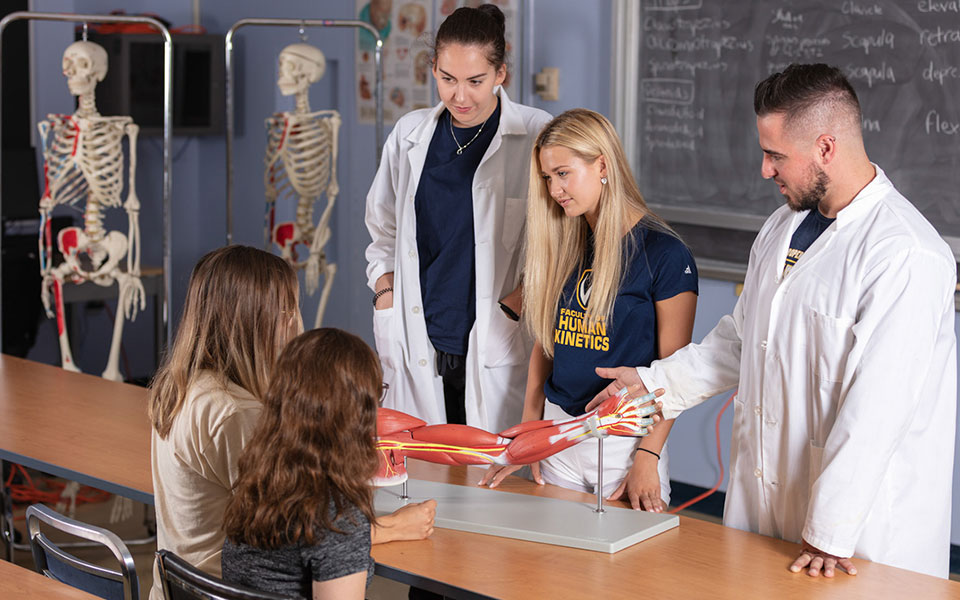 Kinesiology three students showing muscle anatomy to kids in class